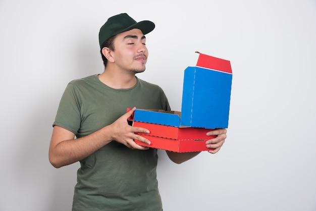 Lieferbote, der pizza auf weißem hintergrund riecht.