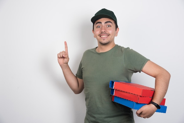 Lieferbote, der pizzaschachteln hält und auf weißem hintergrund zeigt.