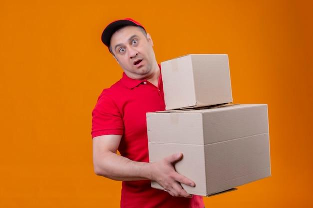 Lieferbote, der rote uniform und kappe hält, die pappkartons hält, schockierte stehend mit weit offenem augenraum