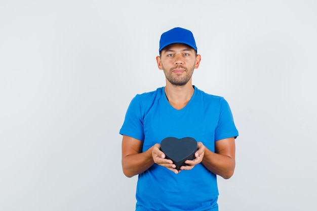 Lieferbote, der schwarze geschenkbox im blauen t-shirt hält