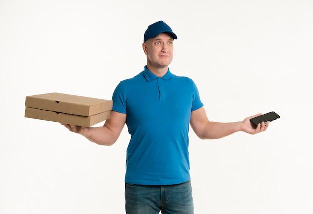 Lieferbote, der smartphone- und pizzakästen hält