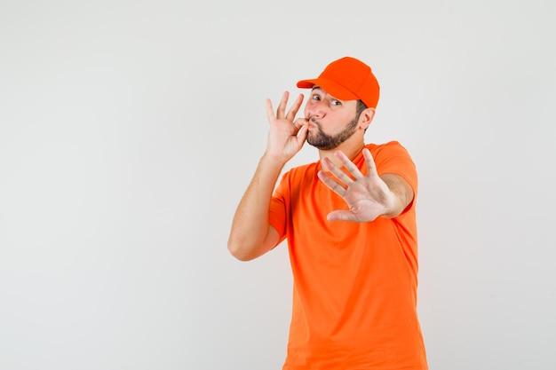 Lieferbote, der stop-geste mit geschlossenem mund als reißverschluss in orangefarbenem t-shirt, mütze und angst zeigt. vorderansicht.