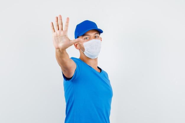 Lieferbote, der stoppgeste mit hand im blauen t-shirt zeigt