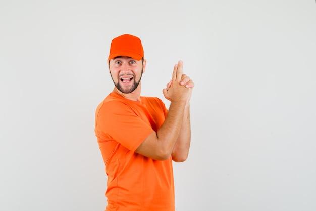 Lieferbote, der waffengeste in orangefarbenem t-shirt, mütze und fröhlichem aussehen zeigt, vorderansicht.