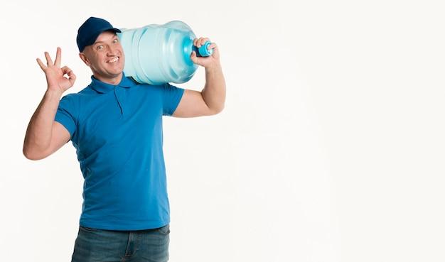 Lieferbote, der wasserflasche hält und okayzeichen macht