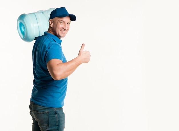 Lieferbote, der wasserflasche hält und sich daumen zeigt