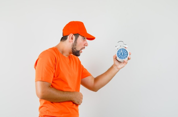 Lieferbote, der wecker in orangefarbenem t-shirt, mütze und aufgeregt schaut. vorderansicht.