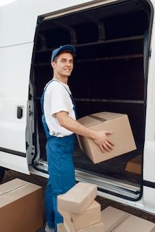 Lieferbote entlädt das auto mit paketen, lieferung