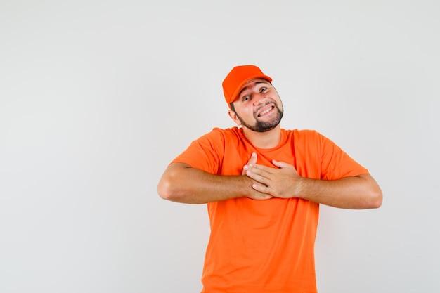 Lieferbote freut sich über kompliment oder geschenk in orangefarbenem t-shirt, mütze und sieht beschämt aus. vorderansicht.