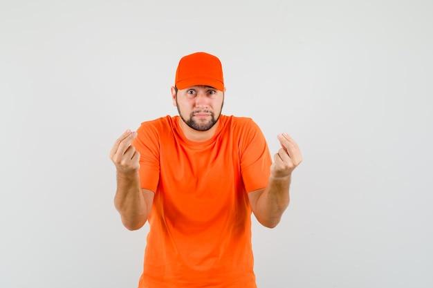 Lieferbote gestikuliert mit zwei fingern in orangefarbenem t-shirt, mütze und schaut ängstlich, vorderansicht.