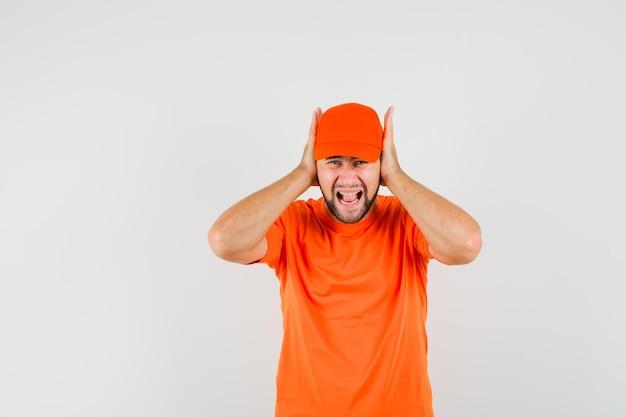 Lieferbote hält die hände an den ohren in orangefarbenem t-shirt, mütze und sieht gereizt aus, vorderansicht.