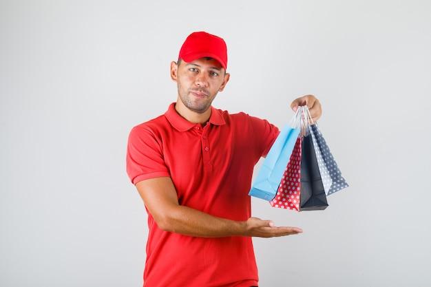 Lieferbote hält farbige papiertüten in roter uniform
