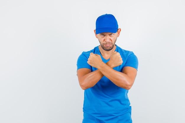 Lieferbote hält geballte fäuste im blauen t-shirt gekreuzt