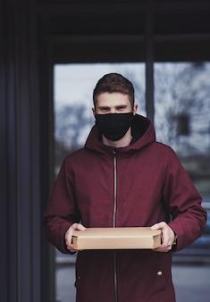 Lieferbote hält pappkarton in maske