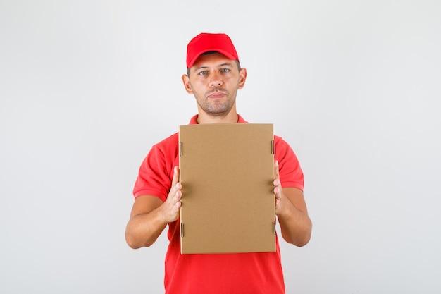 Lieferbote hält pappkarton in roter uniform. vorderansicht.