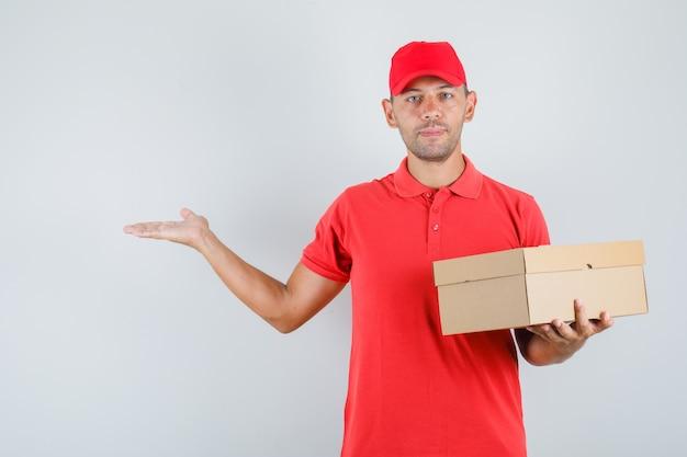 Lieferbote hält pappkarton in roter uniform