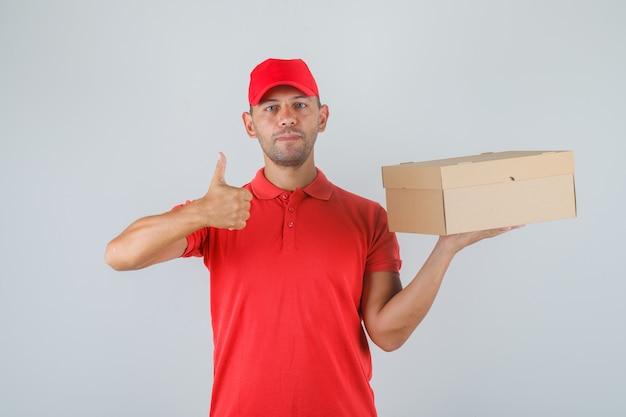 Lieferbote hält pappkarton und zeigt daumen hoch in roter uniform und sieht positiv aus.