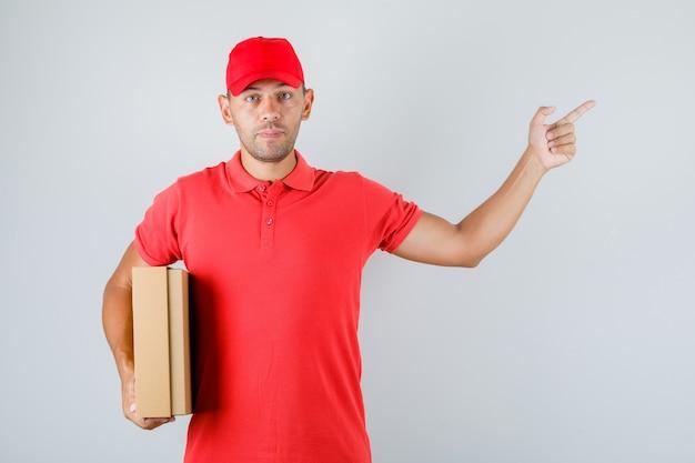 Lieferbote hält pappkarton und zeigt in roter uniform weg
