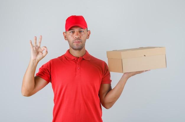 Lieferbote hält pappkarton und zeigt ok-zeichen in roter uniform