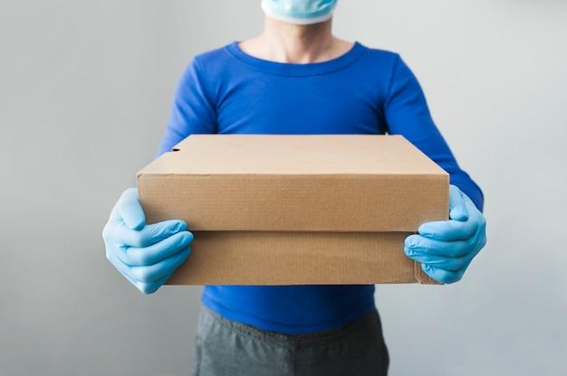 Lieferbote hält pappkartons in medizinischen gummihandschuhen und maske. speicherplatz kopieren