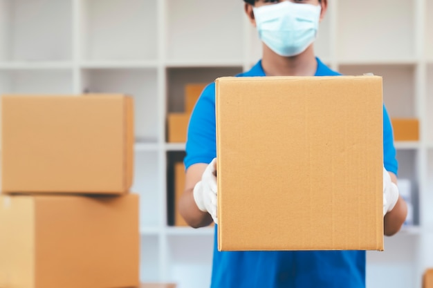 Lieferbote hält pappkartons in medizinischen gummihandschuhen und maske.