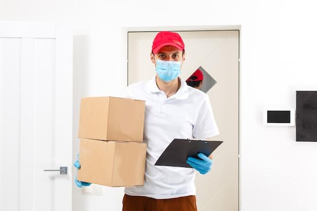 Lieferbote hält pappkartons in medizinischen gummihandschuhen und maske