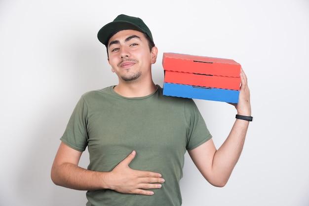 Lieferbote hält seinen bauch und drei schachteln pizza auf weißem hintergrund.