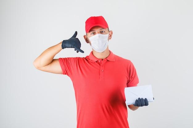 Lieferbote hält umschläge und macht anrufgeste in roter uniform, medizinischer maske, handschuhen, vorderansicht.