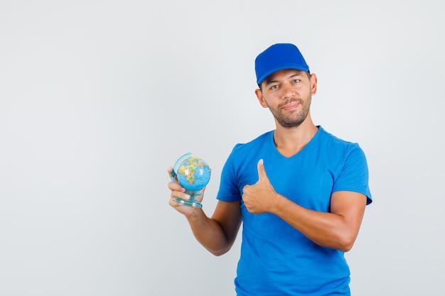 Lieferbote im blauen t-shirt, kappe, die globus mit daumen nach oben hält und fröhlich schaut