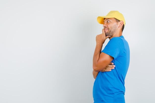 Lieferbote im blauen t-shirt, kappe, die kinn hält und nachdenklich aussieht.