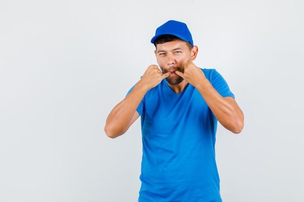 Lieferbote im blauen t-shirt, mütze hageln oder pfeifen
