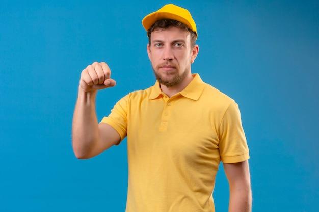 Lieferbote im gelben poloshirt und in der kappe, die faust an der kamera mit stirnrunzelndem gesicht zeigen, das auf isoliertem blau droht