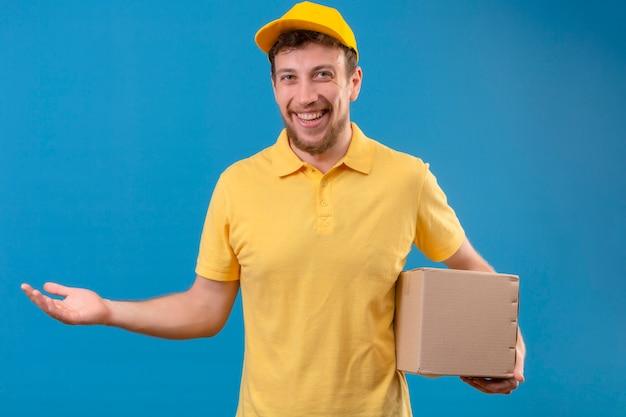 Lieferbote im gelben poloshirt und in der kappe, die kastenpaket darstellt, das mit palme oh seine hand lächelnd freundliches stehen auf lokalisiertem blau präsentiert