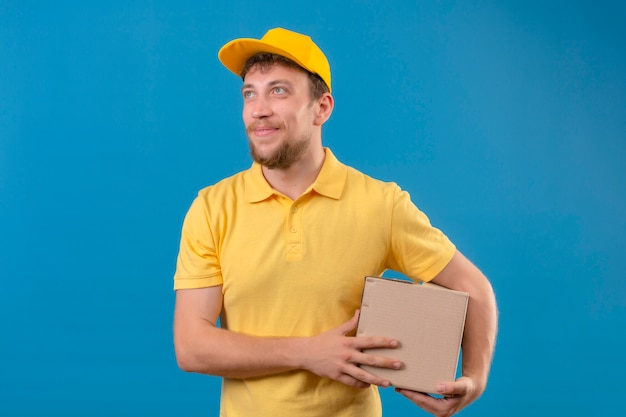 Lieferbote im gelben poloshirt und in der kappe, die kastenpaket in den händen hält, die freundlich lächelnd oben auf blau stehend lächeln