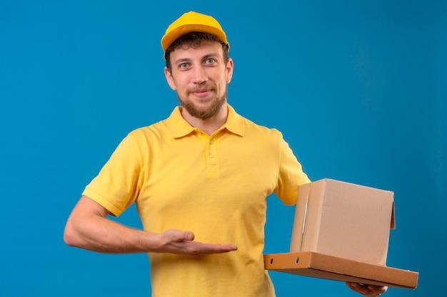 Lieferbote im gelben poloshirt und in der kappe, die pappkartons hält, die freundlich lächeln und mit handfläche oh seine hand präsentieren, die auf blau steht