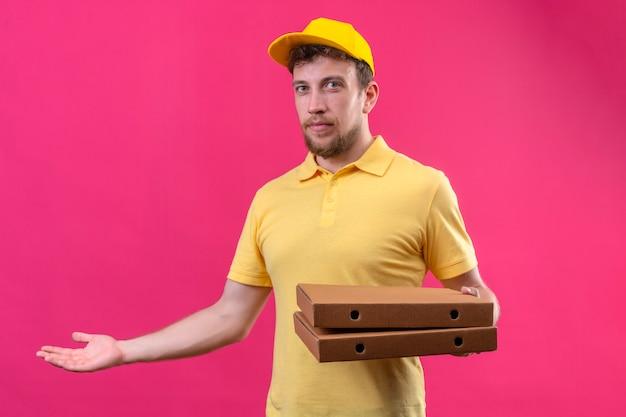 Lieferbote im gelben poloshirt und in der kappe, die pizzaschachteln halten und mit hand und handfläche stehen, die auf rosa stehen