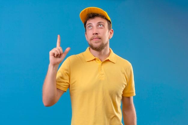 Lieferbote im gelben poloshirt und in der kappe, die sicheres zeigen mit dem finger nach oben und nach oben stehend auf isoliertem blau suchen
