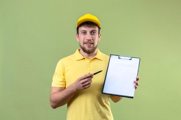 Lieferbote im gelben poloshirt und in der kappe, die zwischenablage mit leerzeichen zeigt, die mit stift zeigen, der um unterschrift lächelt, der auf grün steht