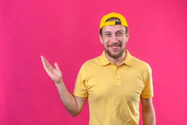 Lieferbote im gelben poloshirt und in der kappe lächelnd fröhlich präsentierend und zeigend mit handfläche stehend auf isoliertem rosa