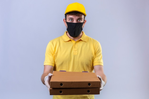Lieferbote im gelben poloshirt und in der kappe tragen schwarze schutzmaske, die pizzaschachteln mit ernstem gesicht hält, das auf weiß steht