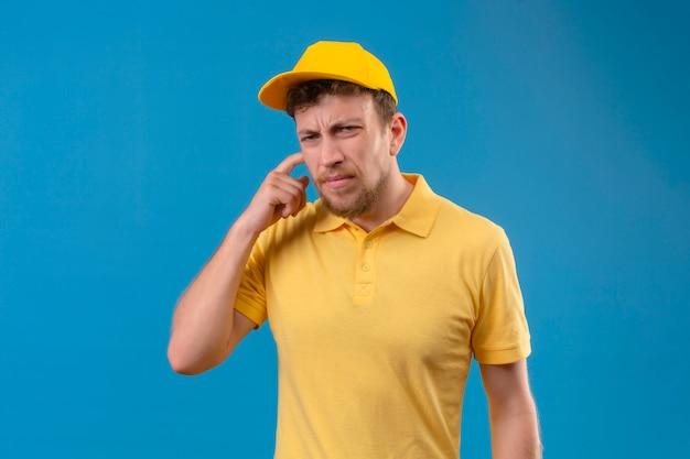 Lieferbote im gelben poloshirt und in der schwerhörigen kappe, die mit finger nahe ohr auf blau lokalisiert stehen