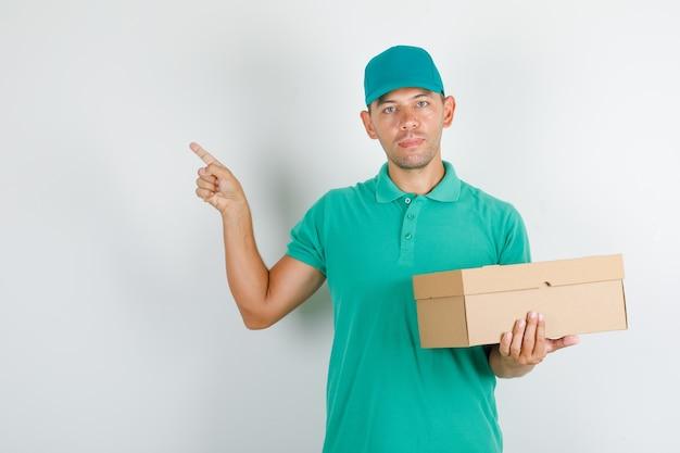 Lieferbote im grünen t-shirt und in der kappe, die etwas mit pappkarton zeigen