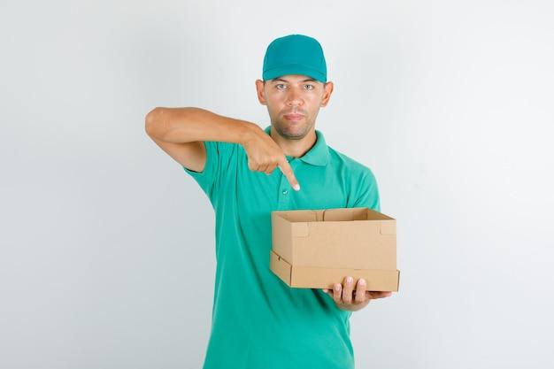 Lieferbote im grünen t-shirt und in der kappe, die pappkarton zeigt
