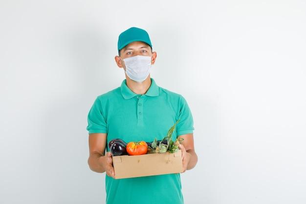 Lieferbote im grünen t-shirt und in der kappe, maske, die gemüsebox hält