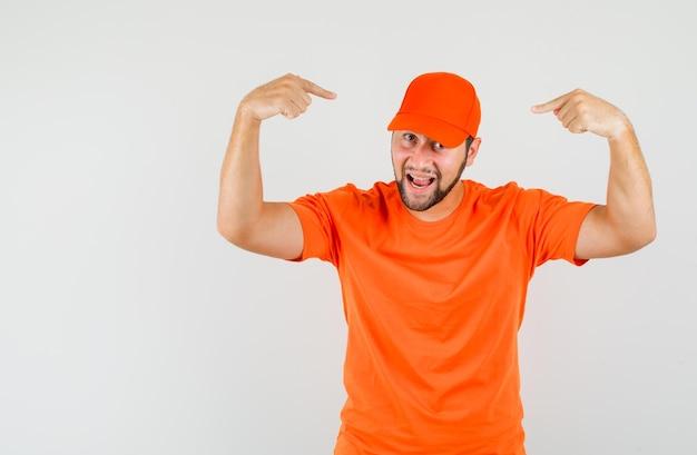 Lieferbote im orangefarbenen t-shirt, das mit den fingern auf seine mütze zeigt und selbstbewusst aussieht, vorderansicht.