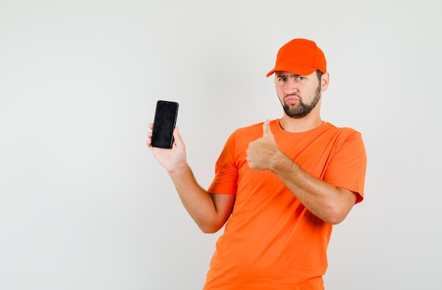 Lieferbote im orangefarbenen t-shirt, mütze hält handy mit daumen nach oben und sieht düster aus, vorderansicht.