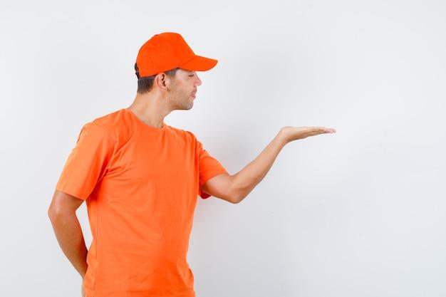 Lieferbote im orangefarbenen t-shirt und in der kappe, die erhabene handfläche ausbreiten, andere hand verstecken und joker schauen, vorderansicht.