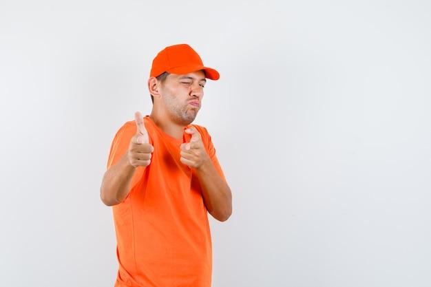 Lieferbote im orangefarbenen t-shirt und in der kappe, die waffengeste nachahmt