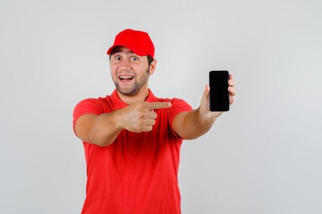 Lieferbote im roten t-shirt, kappe, die auf smartphone zeigt und fröhlich schaut