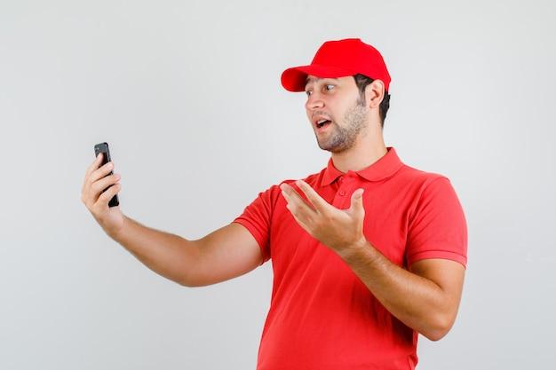 Lieferbote im roten t-shirt, kappe, die auf videoanruf spricht und emotional schaut